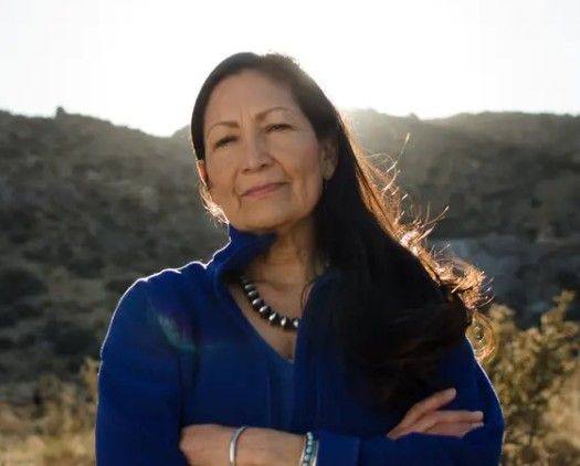 Rep. Deb Haaland standing in her State backlighted by the sun.