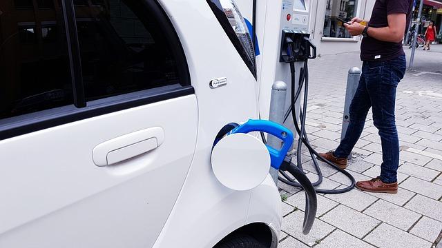 White car charging while man checks phone.
