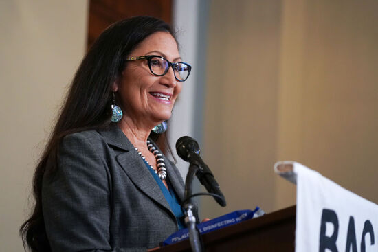 Deb Haaland. Secretary of the Interior. Standing, smiling from behind microphone/podium.