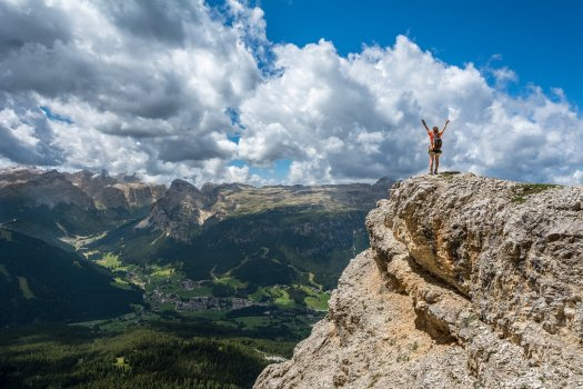 Person with arms raised over head standing on a mountain top.