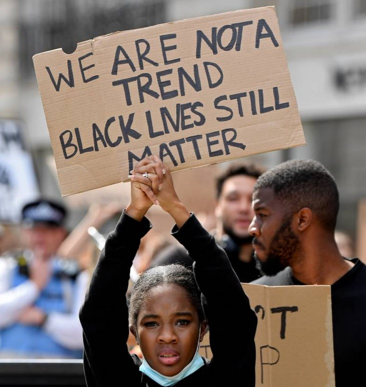 A protestor holds up a sign during BLM march in London, Britain, June 28, 2020.