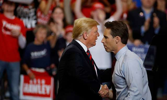 Pres. Trump shakes hands with Senator Josh Hawley on stage of rally.