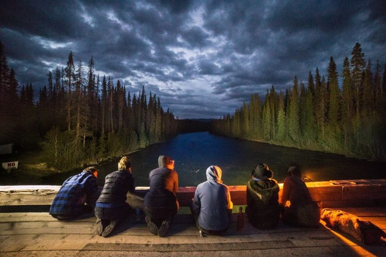 Six people at dusk on wooden bridge, trees line river out of site.