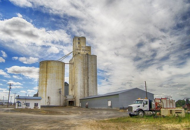 Rural agriculture industry with warehouse, trucks and grain silos.