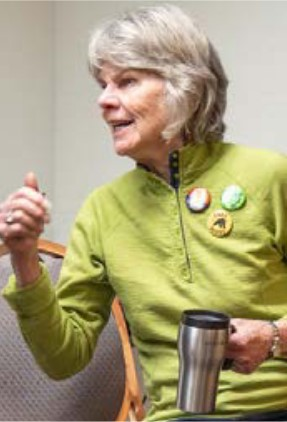 Photo of the author, Bobbi Righi. Gray medium-length hair and green top with multiple pins/buttons..