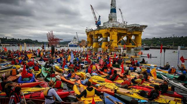 Seattle Kayaktivists protest Arctic drilling. By Joshua Trujillo. Yellow oil platfom surrounded by kayaks.