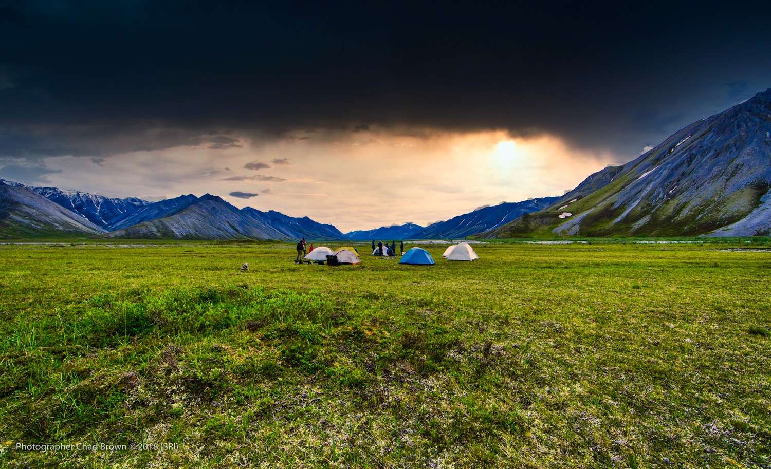 Arctic meadow surrounded by mountains, dark sky.