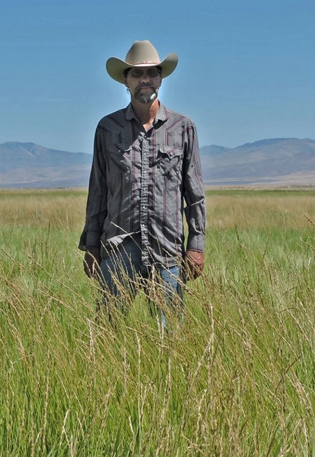 Farmer Edward Bartell stands in a tall-grass field, mountains behind.