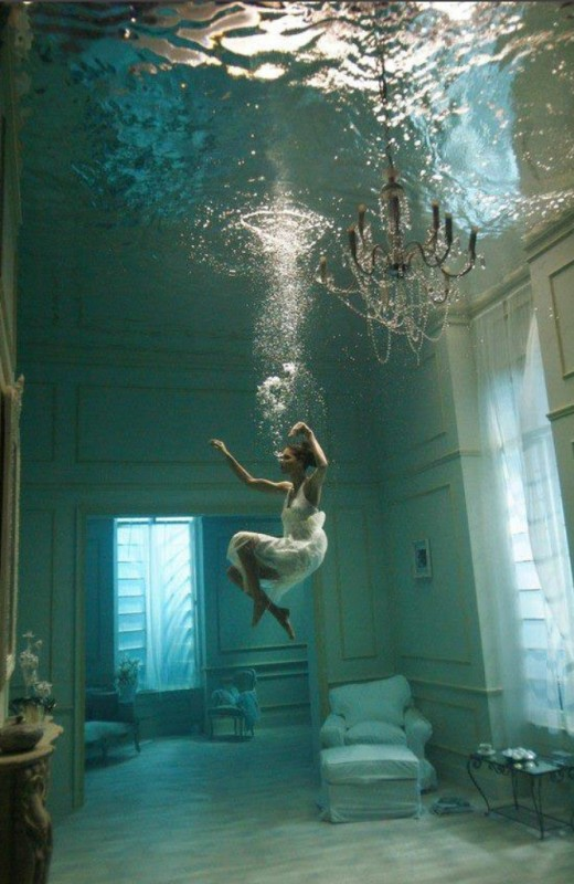 A woman floating in her livingroom full of water.