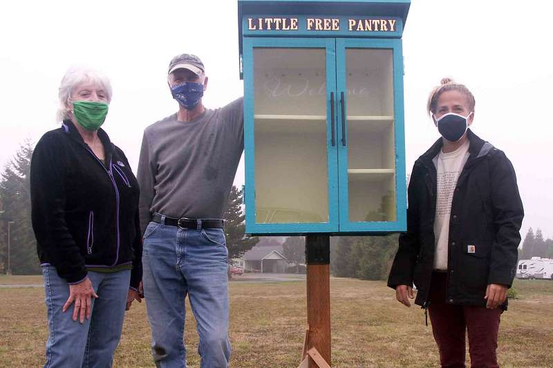 Three folks posing around new pantry with masks on.