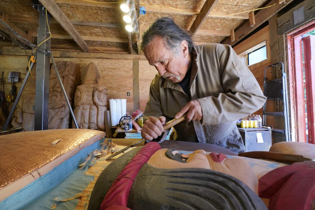 Wood carver Jewell James works on a totem pole.