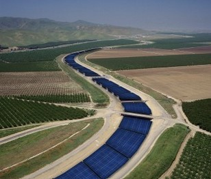 Solar panels covering a water aqueduct snaking among planted fields.