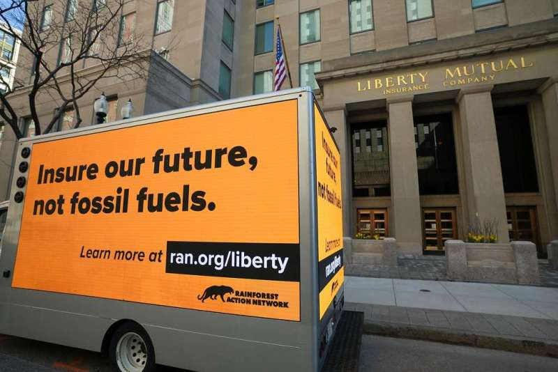 Insure our future, not fossil fuels. On yellow sides of truck box, in front of Liberty Mutual.
