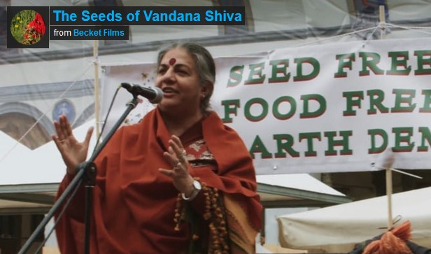 From the film The Seeds of Vandana Shiva. Vandana speaking onstage, smiling and imploring.