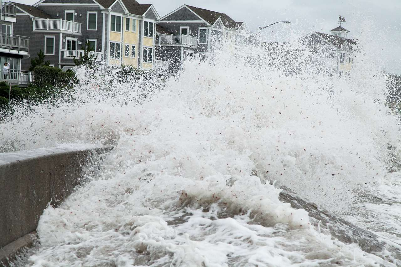 Close-up from the water side, of a wave breaking over a shore barrier in front of houses.