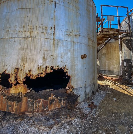 Decaying oil tanks with large rusted holes, making the tank look like a helmet with eyes.