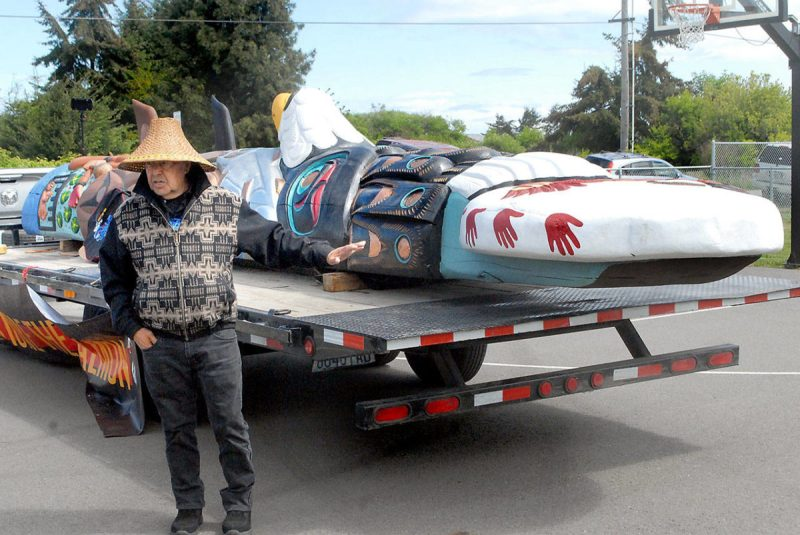 Lummi Nation totem carver Sit ki kadem, also called Doug James, explains the meaning of the elements of a totem that is traveling the United States on its way to Washington, D.C., during a stop on Tuesday at the Lower Elwha Reservation near Port Angeles.