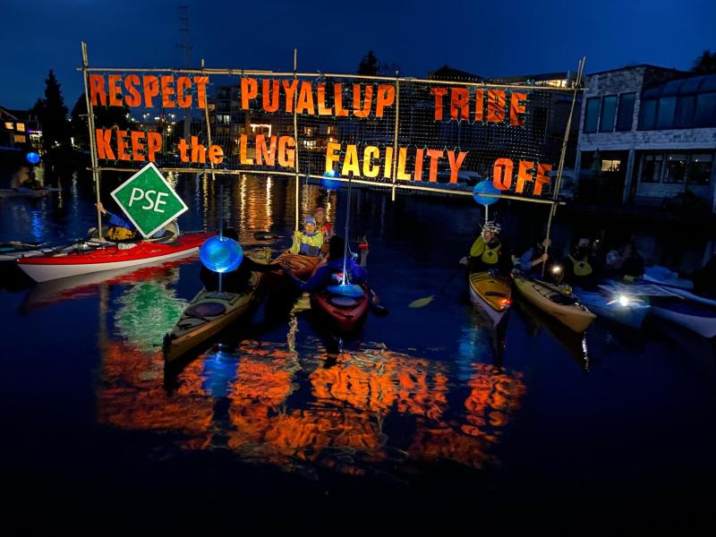Line of Kayaktivists holding banner, late dusk, reflecting in the water -- Respect Puyallup Tribe. Keep the LNG Facility OFF!