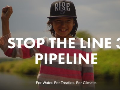 Stop the Line 3 Pipeline. Smiling indigenous youth holding-up a fist.
