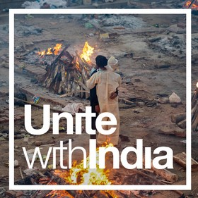 Unite with India. Two people hugging in a yard of pyres.