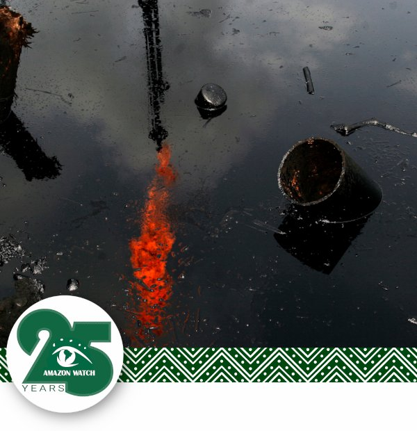 Amazon Watch. Burn-off flame reflected in a lake of oil and debris.