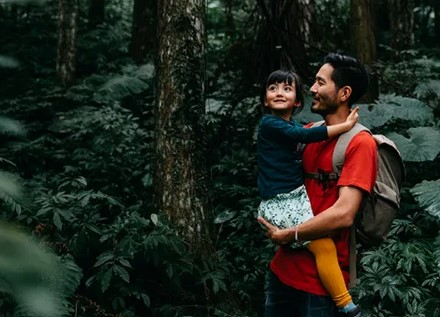 Man holding daughter in forest.