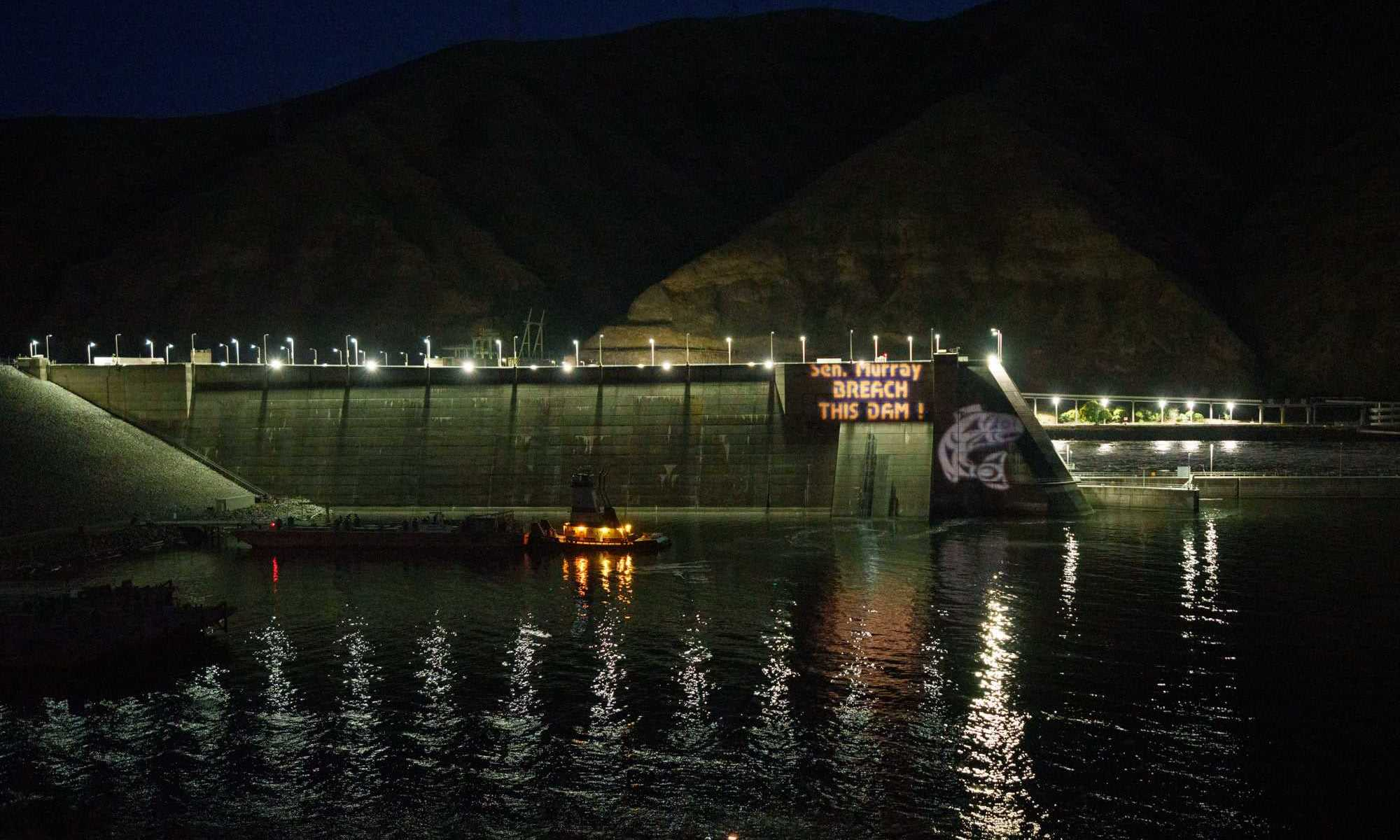 Snake River dam showing protest projection at night. Sen. Murray, Breach this Dam!