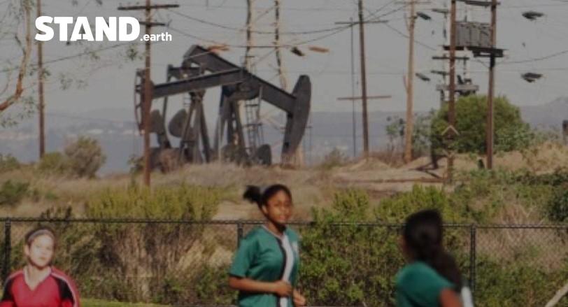 Girl's PE next to oil pump jacks.