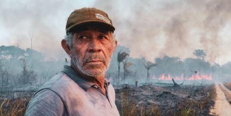 Man with burning forest behind.