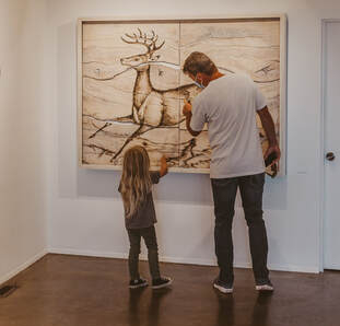 Father and daughter examining a painting.