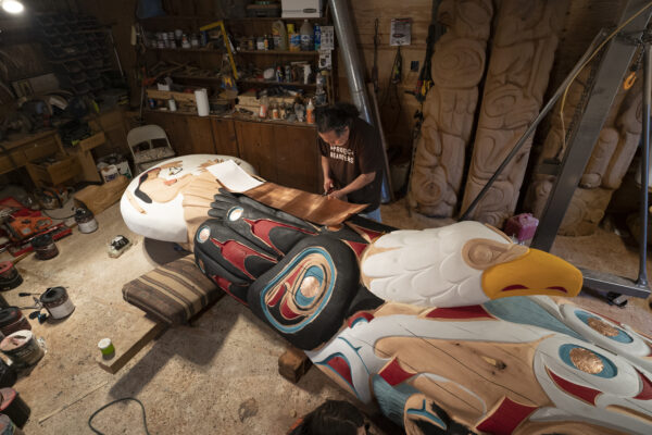 A man carving a special horizontal totem pole.