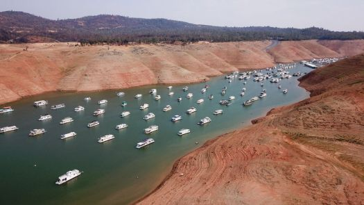 Lake Oroville, CA with houseboats nearly stranded in what looks like a river.