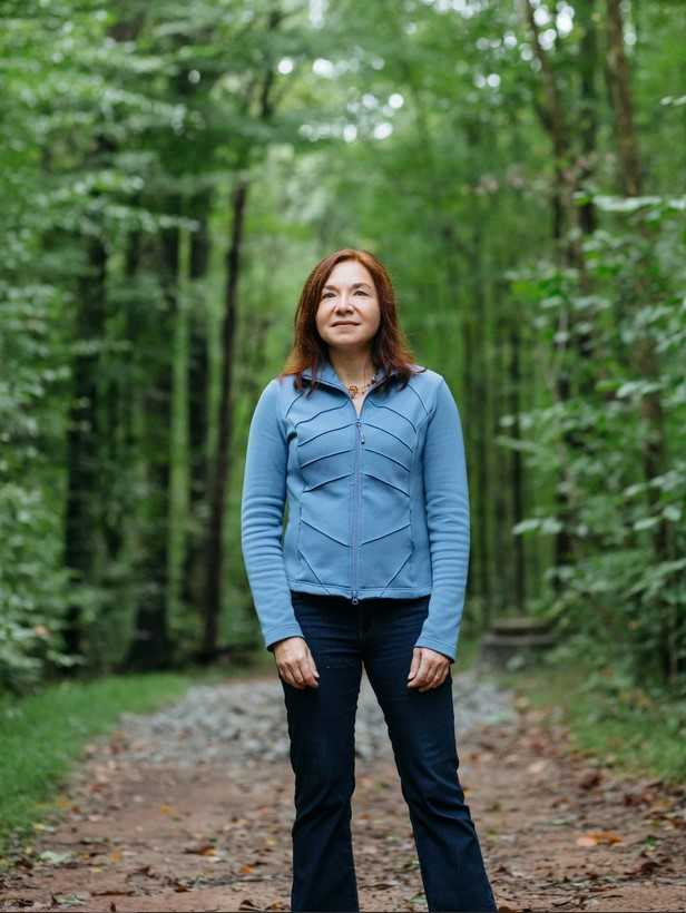 Katharine Hayhoe Photo standing in a forest path.