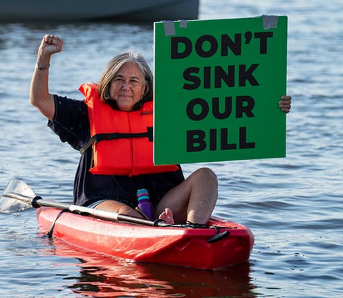 Woman in kayak holding sign, Don't sink our bill.